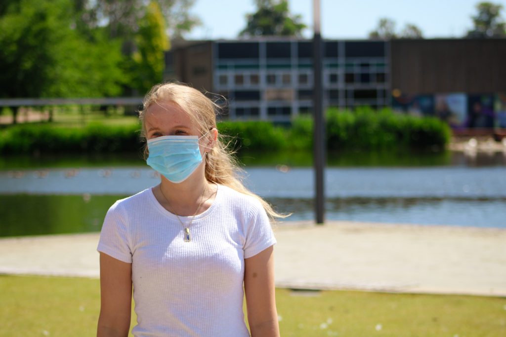 Girl looks across Greg's place in blue medical mask