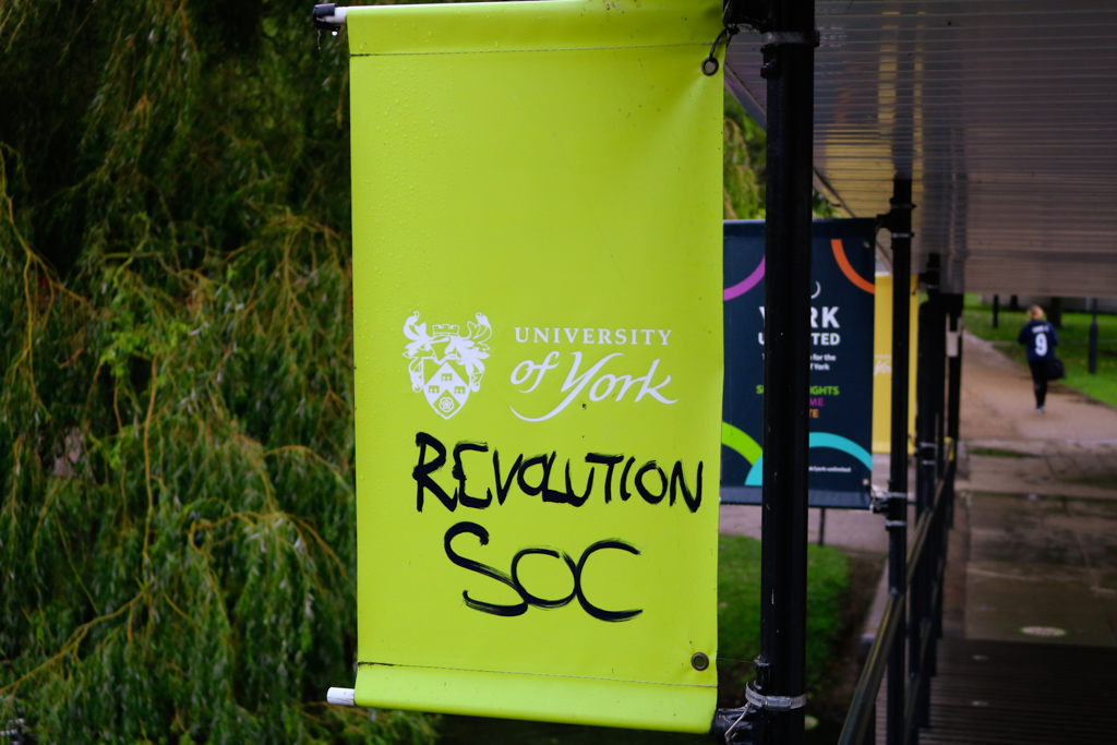 "University of York signs over Central Hall bridge graffitied with ""Revolution Soc"""