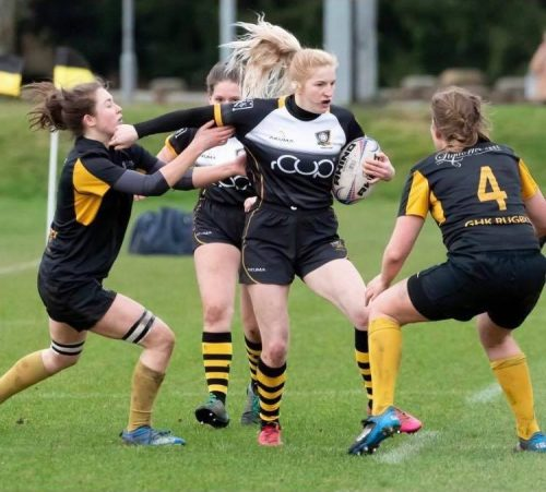 York women's rugby player hands off opposition as they storm through defences
