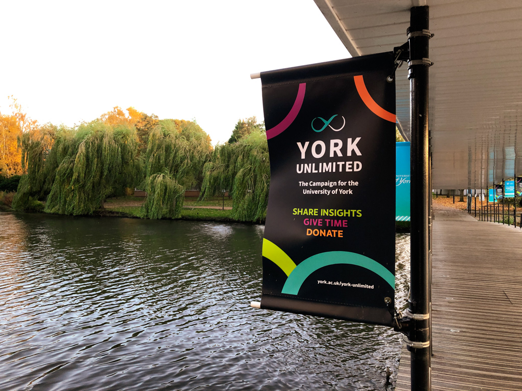 York Unlimited sign on bridge next to Central Hall, overlooking lake